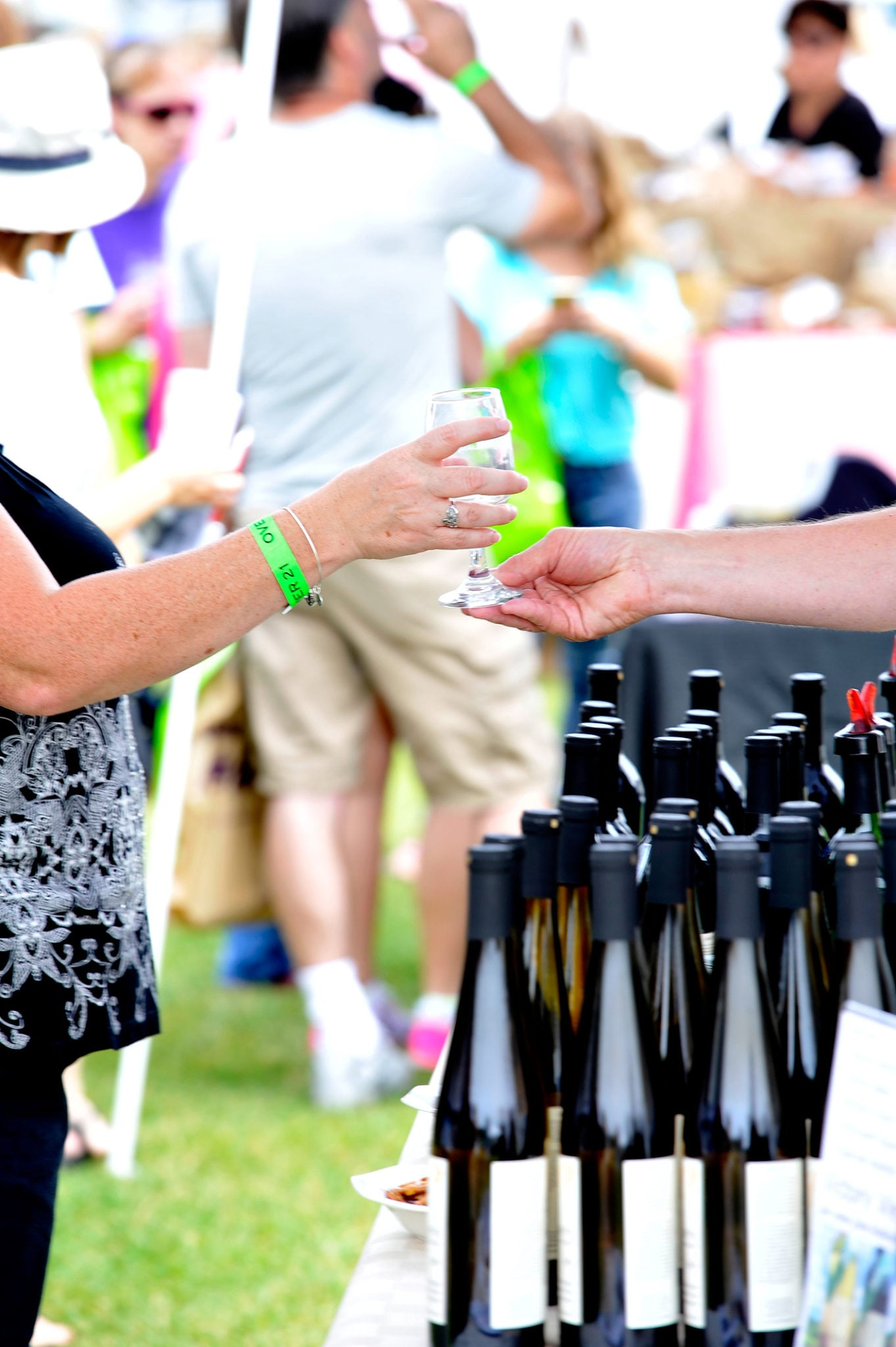 woman-handing-glass-to-wine-vendor-to-be-poured
